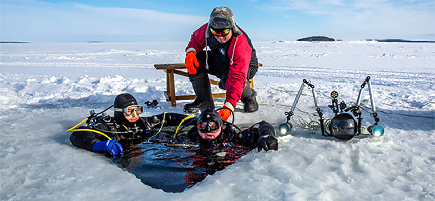 Divers with hole in sea ice